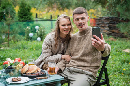 A young couple quarantined during covid-19 at their country home get in touch via video call with their parents. Picnic in nature on self-isolation. Banque d'images