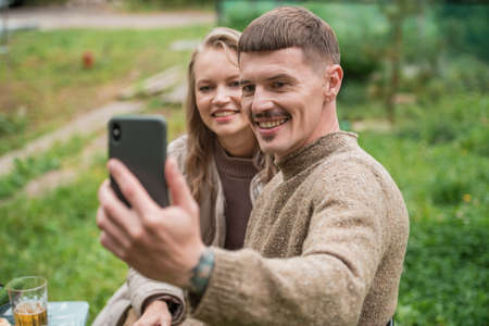 A young beautiful couple take photos of their new country house on a smartphone camera. Picnic in nature on the occasion of the purchase of real estate in the country.
