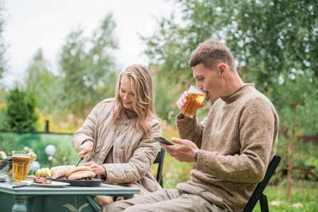 A man and a woman young adults made a picnic to relax in the open air in the courtyard of a country house. Chill sitting at a table with smartphones in hand.