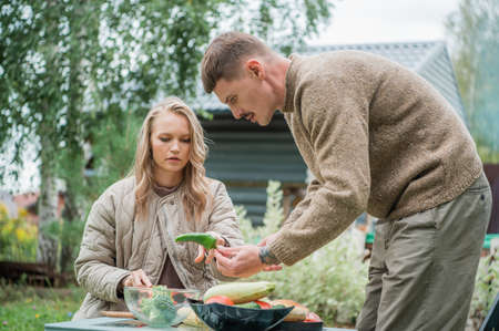 Young people cut vegetables with a knife on a cutting Board. Prepare for an outdoor barbecue and wait for guests to visit.