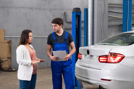 Woman talking to car service worker about car repair Banque d'images