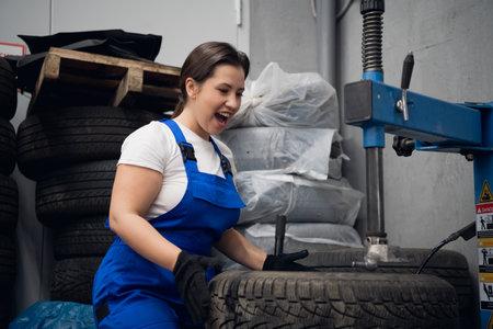 Mechanic repairing a car wheel using a press