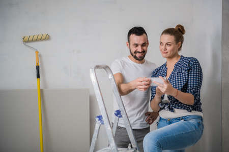 Man and his girlfriend sitting on a stepladder and looking at photos on the phone