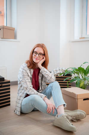 In a new white light apartment, a girl sits on the floor and poses against a background of cardboard boxes and a potted flower Standard-Bild