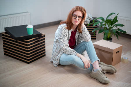 A tired girl in glasses, casual clothes and jeans sits on the floor in her new apartment and dreams of a new life Standard-Bild
