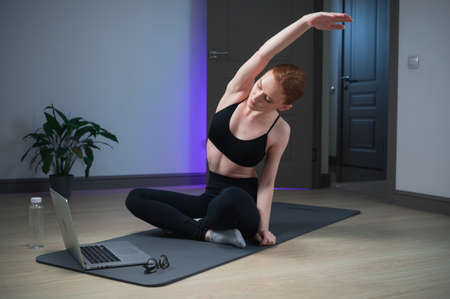 Stretching exercises are an important part of online training in the course on body balance, the girl is engaged on the mat at home in front of the laptop