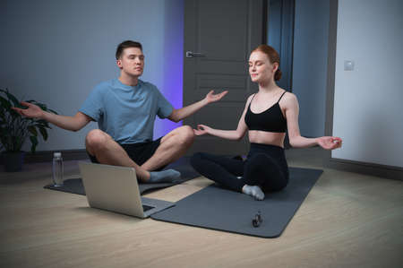 A husband and wife spend a yoga class at home sitting on the floor, they meditate together in front of a laptop