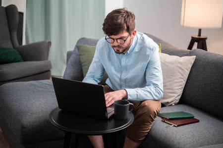 A bearded man with glasses works from home, sitting on the sofa in front of a coffee table with a laptop and a cup of coffee