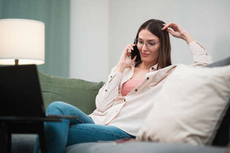 A pretty girl got a call from her boyfriend while working remotely from home, she is talking on the phone and smiling