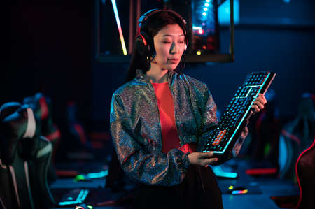 An experienced esports girl advertises a new gaming keyboard in the neon light Standard-Bild