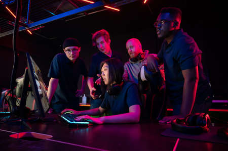 Asian girl playing in a computer club, guys standing behind and prompting