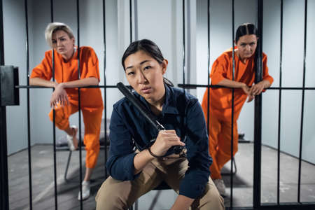 Portrait of an asian security guard against the background of two cute criminals in the cells