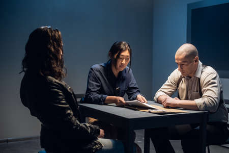 In the police stations interrogation room, good and bad cops are questioning a theft suspect in a leather jacket. Standard-Bild