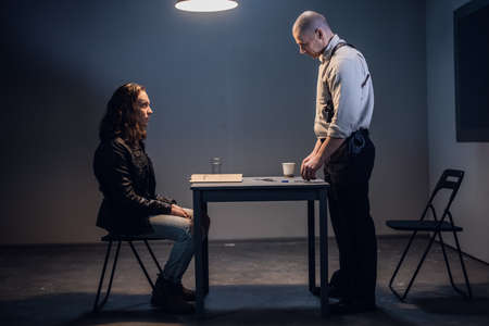 A police investigator manipulates evidence in a case to frame a detained man sitting at a table in handcuffs.