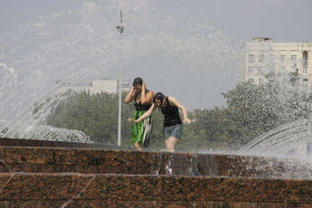 Moscow. Hot summer. Girls in the big city fountain saved from heat. July 23, 2010.