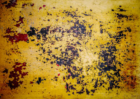Rust on yellow painted metal surface. Through the peeling and cracked paint show through the layers of previous paint layers, and the iron surface.