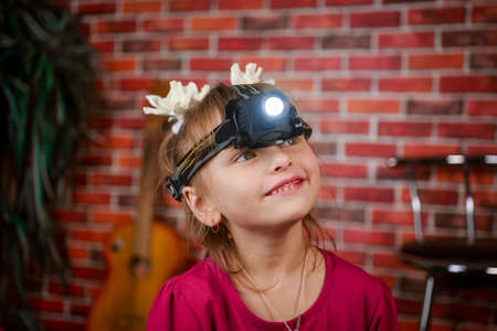 A little girl wearing a flashlight on his head and stands on brick wall background