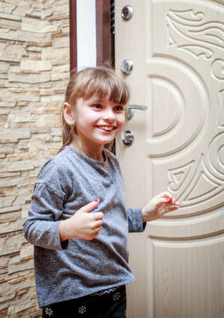 A little girl stands in the hallway of the apartment near the front door and smiles. Stock Photo