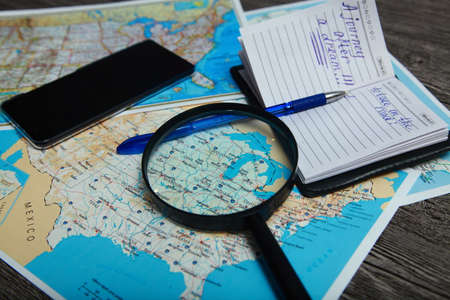 On the table is a map of the United States, phone, pen, magnifier and notebook. People are preparing to travel. Stock Photo