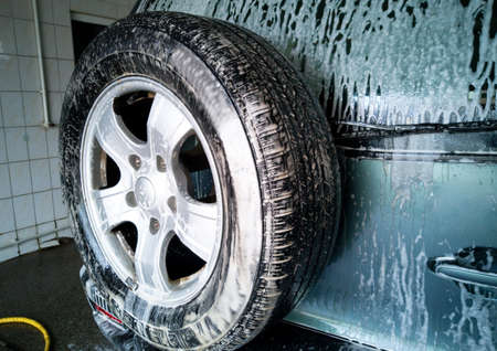 Car wash. Foam drains down and dissolves dirt on the rear door and spare wheel of the car.