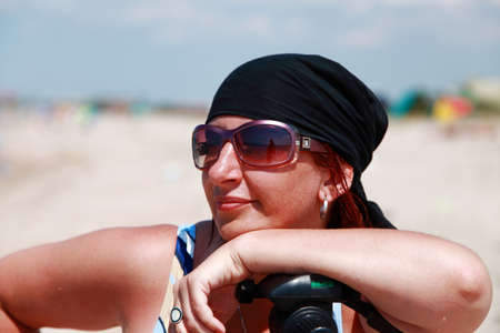 Tanned girl in a black bandana and a swimsuit is on the beach leaning on a photographic tripod.