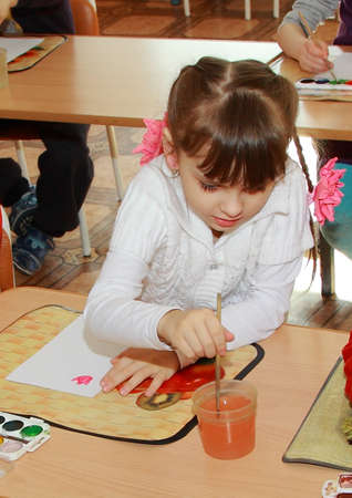 The lesson in kindergarten. Girl paints on a sheet of paper.