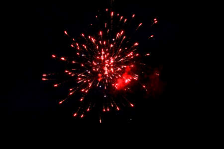Festive fireworks illuminate the night sky with red lights.