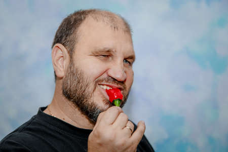 A man likes red chili peppers. He bites it.