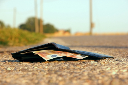 lost wallet at the edge of a asphalted road Standard-Bild