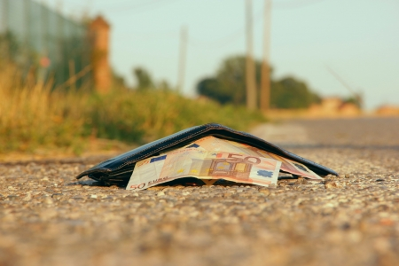 lost wallet at the edge of a asphalted road Stock Photo