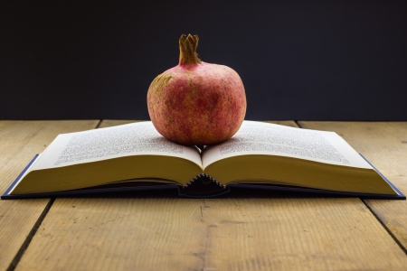 Book with a pomegranate on the wooden table  photo