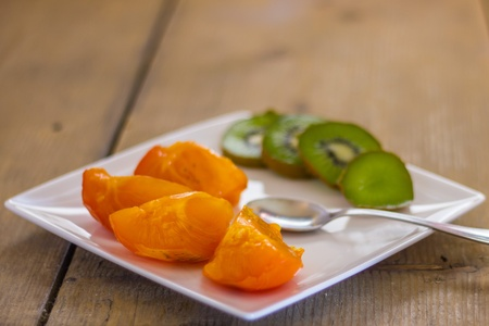 A plate of persimmons with kiwi photo