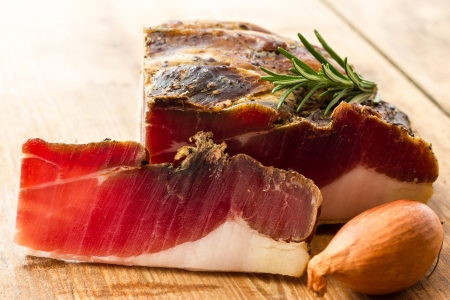Tasty slices of Italian speck with rosemary photo
