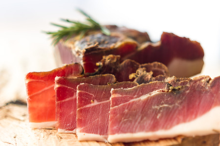 Tasty slices of Italian speck with rosemary