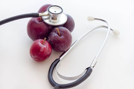 Red prunes with stethoscope Stock Photo
