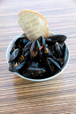 Peppery mussels with lemon and bread Фото со стока
