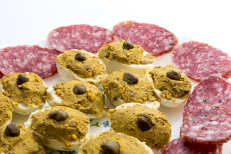 Appetizer with stuffed eggs and sliced salami
