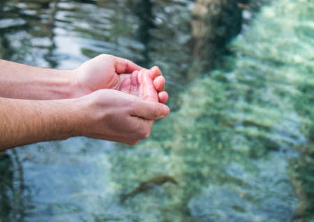Sunny day of person enjoying with crystal clear lake water in hands