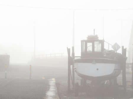 waits: A boat waits for its tour in the foggy harbor