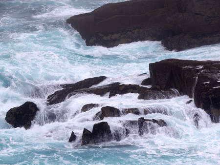 Wild waves crashing against a rock on Dingle peninsula, Ireland