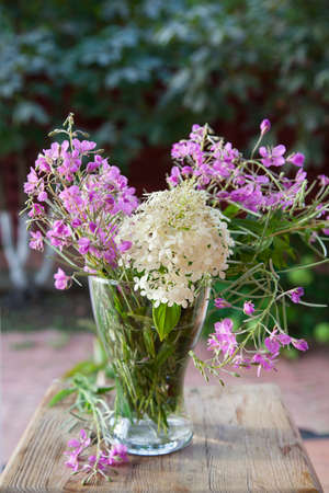 fireweed: Bright summer bouquet of white hydrangea and fireweed in a glass vase