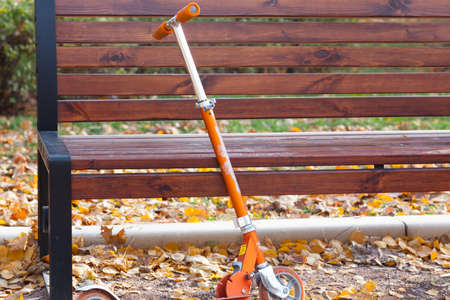 Kids kick scooter left at the bench in an autumn park photo