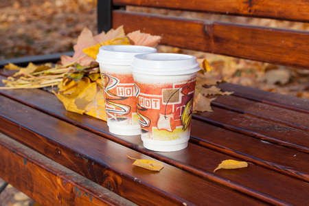 Two paper cups with hot coffee or tea on a bench in an autumn park photo