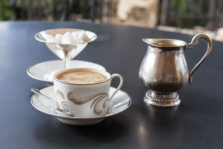 creamer: A cup of coffee, silver creamer and sugar bowl on the table on open veranda