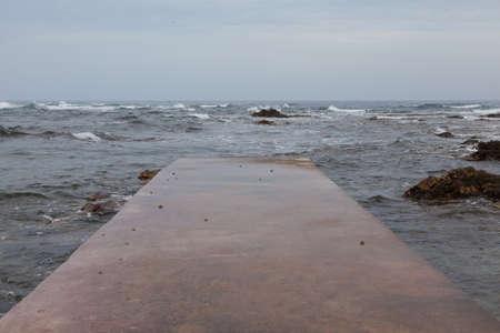 restless: Granite pier on the restless sea Stock Photo