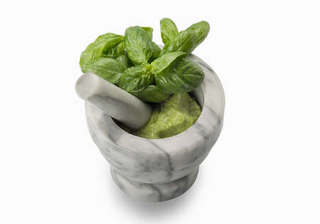 Carrara marble mortar and pestle with Genoese Italian pesto and green basil leaves, isolated on white background Archivio Fotografico