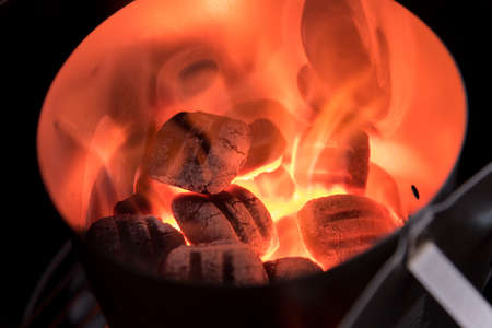 Charcoal Briquettes for barbecue lights up in Chimney Starter Stock Photo