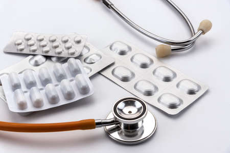 blisters of pharmaceutical medicines in capsules and pills for therapy and stethoscope on the white background