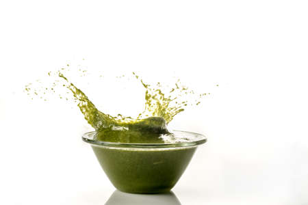 Genoese pesto splashes out of a clear glass bowl, still