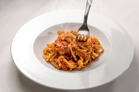 spaghetti egg based (Italian tagliatelle) topped with meat and tomato sauce whit fork, steamed in a plate on white background